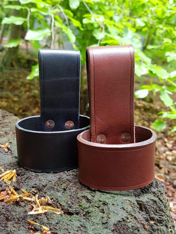 two leather axe loops in black and brown on tree stump