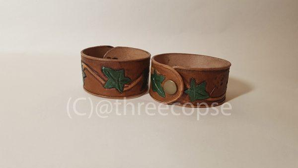 two hand carved Ivey pattern cuffs in leather one showing a snap fitting