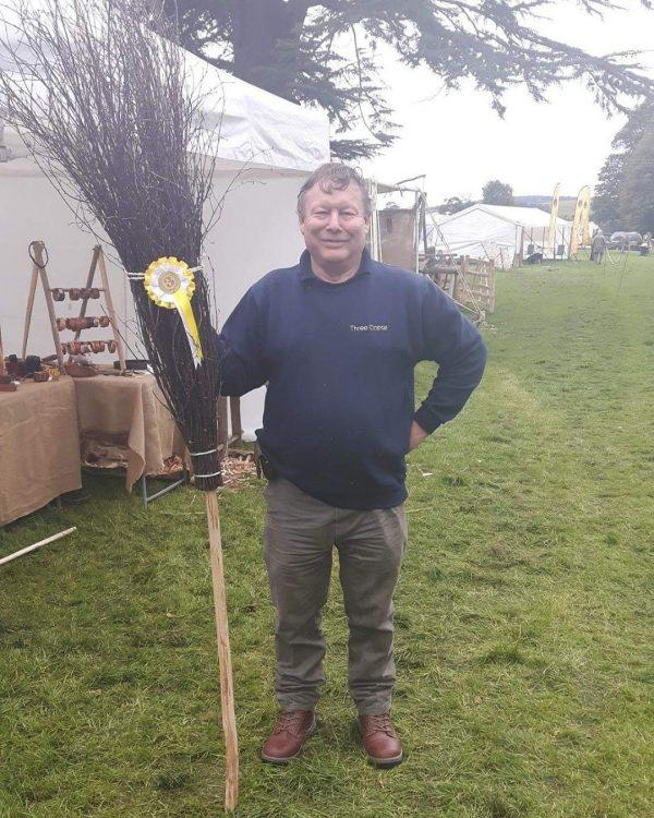Man standign with besom broom the broom has a prize ribon atached to it