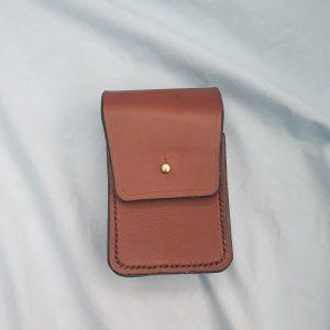 a samll brown pouch with a brass sma brown stud to hold the flap closed it has black stitiching around the edge