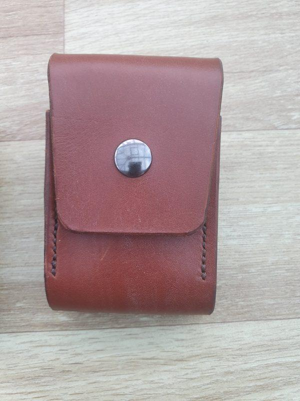 a brown leathe pouch with a squar flap cover in the center is a button snap