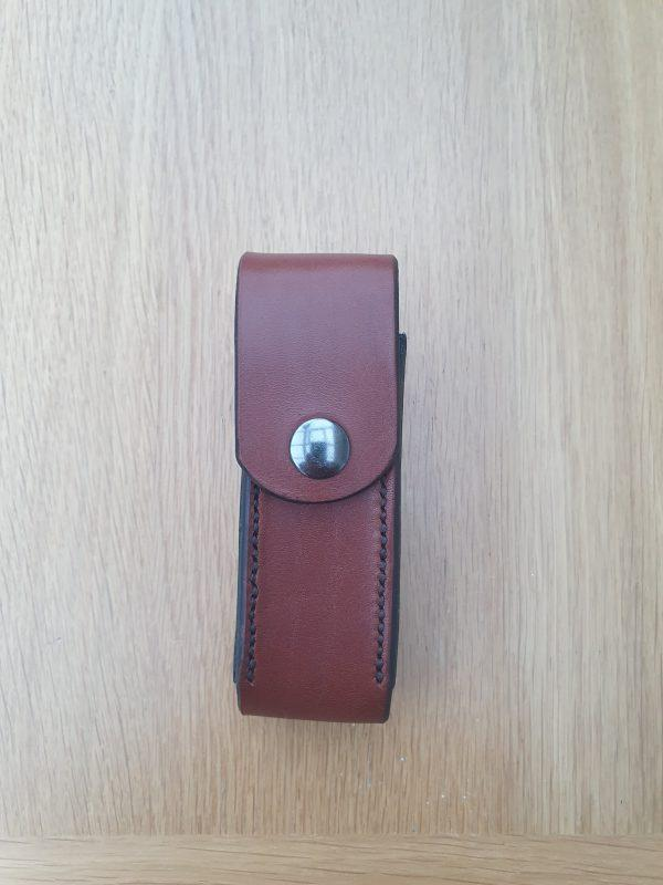 a small brown leather pouch with black stitching and a gun mental grey snap