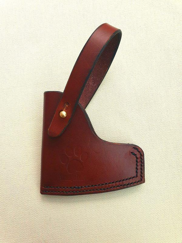 Brown axe sheath with brass stud on white back groundd
