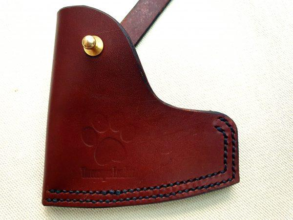 Brown axe sheath with brass stud on shite back ground